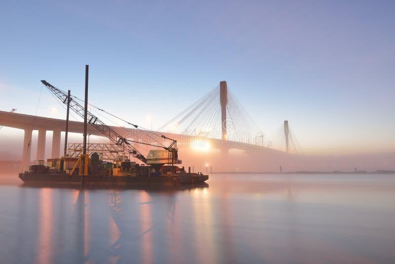 在日出的新的口岸曼桥梁和小船举的起重机 免版税图库摄影