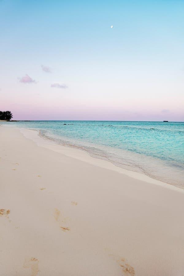 在日出的月亮在海滩 免版税库存图片