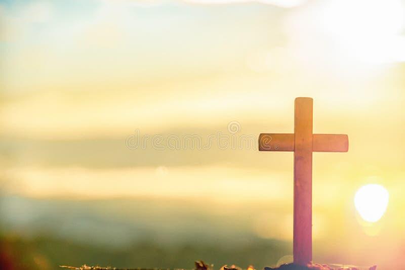 在日出的木十字架在早晨时间有圣洁和轻的背景 耶稣基督标志宽容宗教概念在十字架上钉死  免版税库存图片