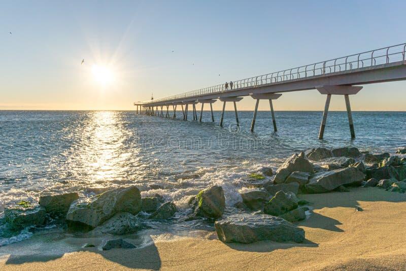 在日出的海桥梁与岩石 库存图片