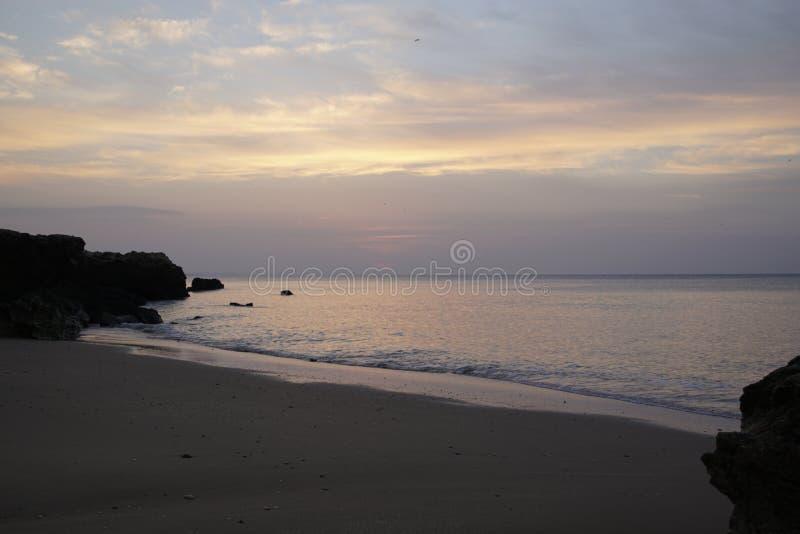 在日出的海洋 atlantes 在美丽的鸟云彩之上颜色及早飞行金子早晨本质宜人的平静的反映上升海运一些星期日 黑色岩石 展望期 库存图片