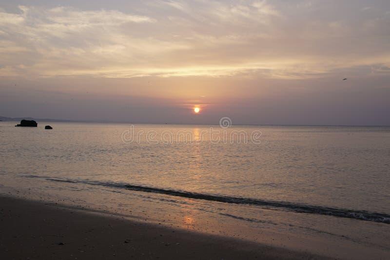在日出的海洋 atlantes 在美丽的鸟云彩之上颜色及早飞行金子早晨本质宜人的平静的反映上升海运一些星期日 黑色岩石 展望期 库存照片