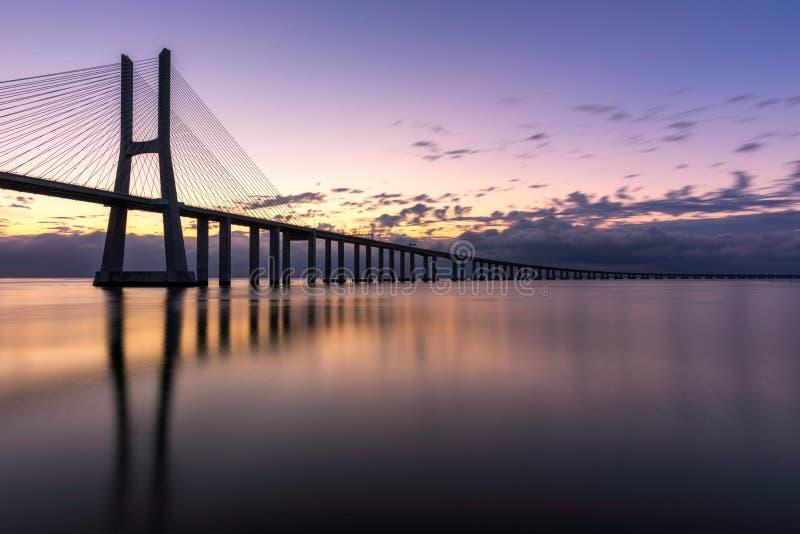 在日出的瓦斯科・达・伽马桥梁在里斯本,葡萄牙 华士古达伽马大桥是高架桥侧的一座缆绳被停留的桥梁和 图库摄影