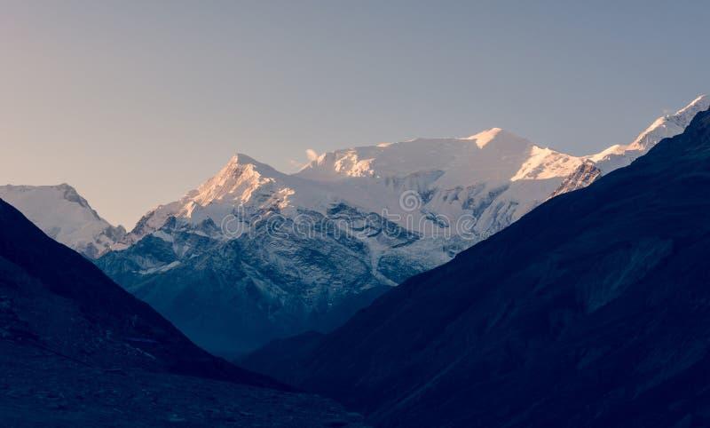 在日出的积雪的山土坎 免版税库存照片