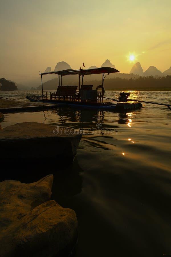 在日出的竹木筏 免版税库存照片