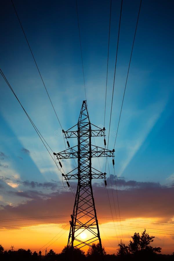 在日出的输电线 免版税库存图片