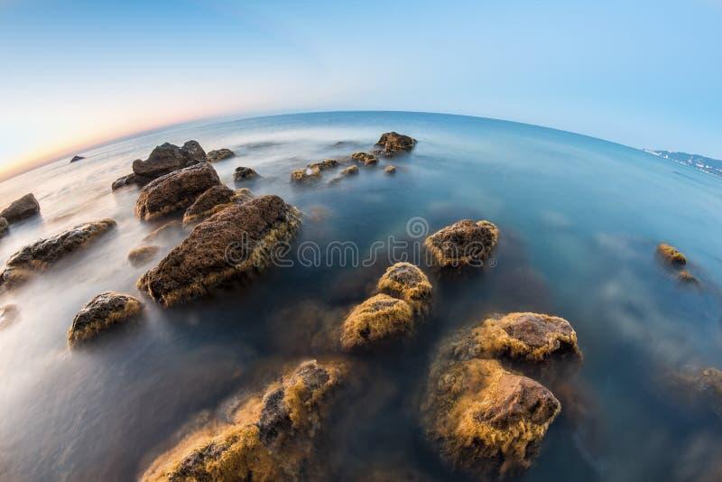 在日出的水下的岩石在海滩 免版税图库摄影