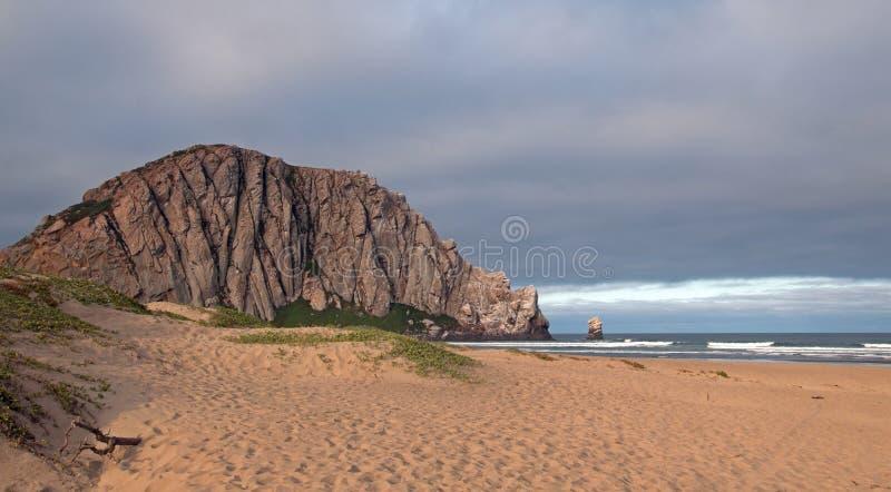 在日出的Morro岩石在莫罗贝国家公园野营的斑点的积云下在中央加利福尼亚海岸美国 免版税库存照片