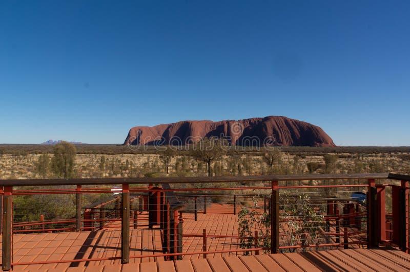 在日出的Uluru在美丽的天空蔚蓝和看法平台,Uluru卡塔Tjuta国立公园,北方领土,澳大利亚下 库存照片