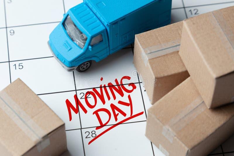 在日历的移动的天在红色被写 与笔记的日历与纸板箱和卡车 库存照片