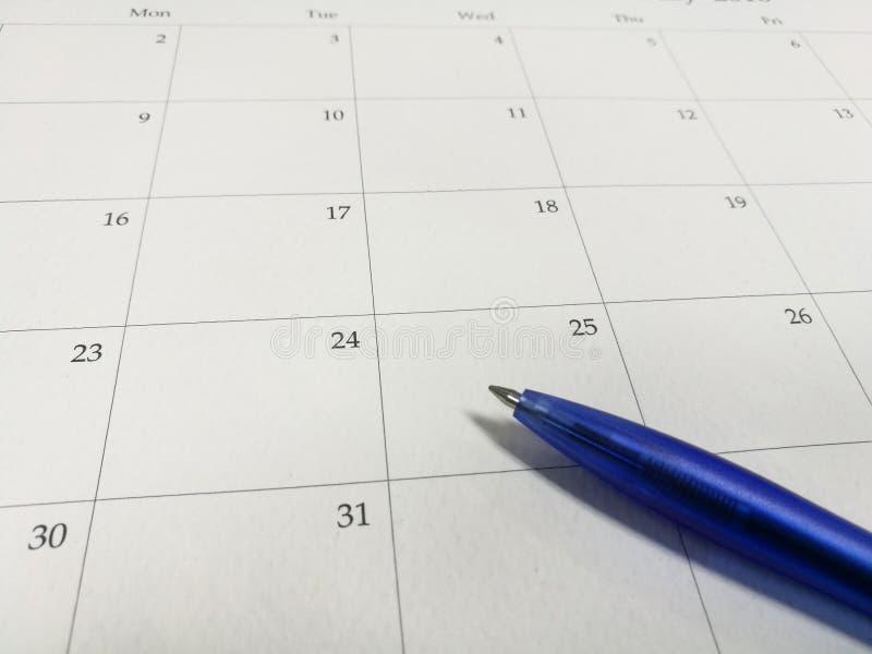 在日历的蓝色圆珠笔,日历背景 库存照片