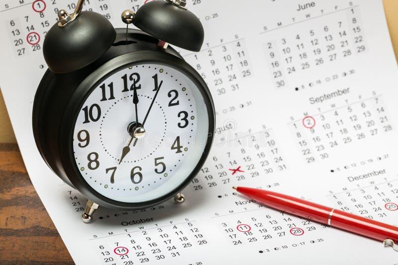 在日历背景的黑闹钟 免版税库存照片