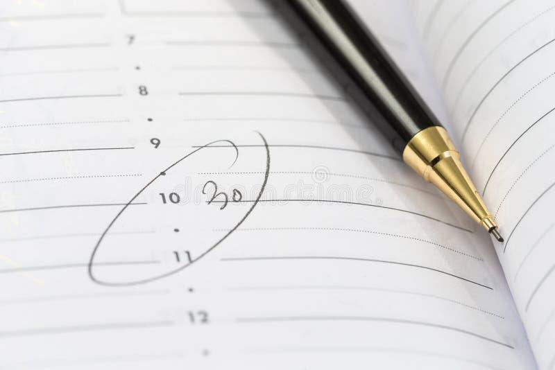 在日历页的笔 说谎在议程中的圆珠笔与盘旋的小时  免版税库存图片