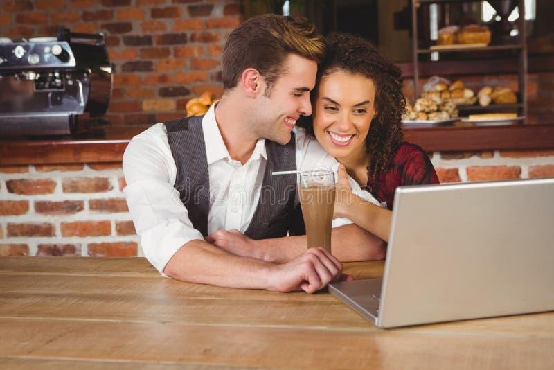 在日期观看的照片的逗人喜爱的夫妇在膝上型计算机 免版税库存图片