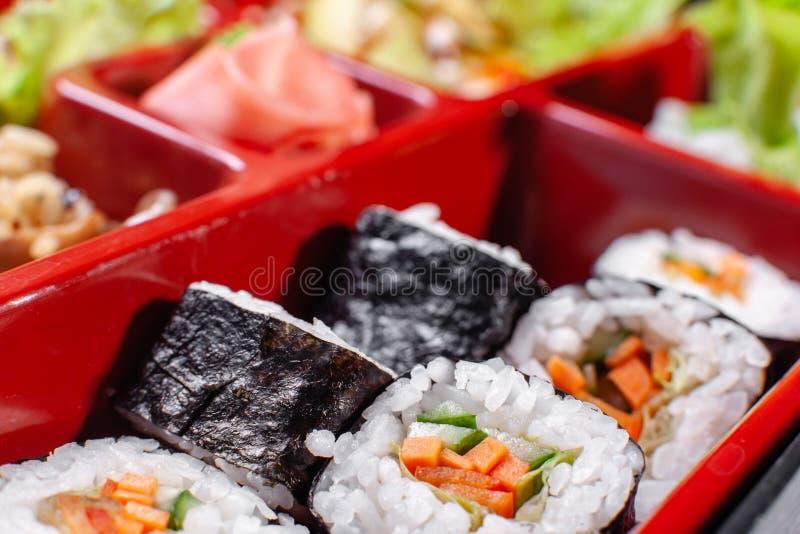 在日本bento箱子的新鲜食品部分用沙拉,主菜 与菜的寿司卷 豆黄瓜断送素食新鲜的油煎的骨髓的蕃茄 免版税库存图片