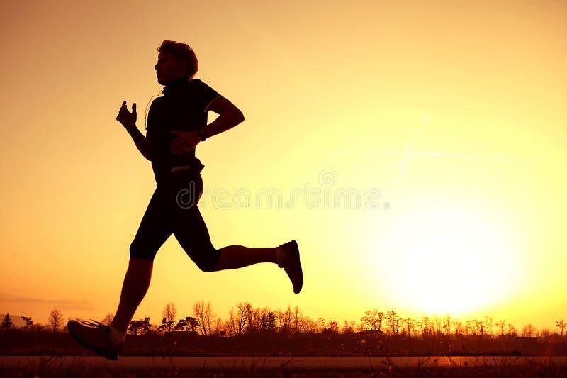 在日落上升的剪影赛跑者 免版税库存照片