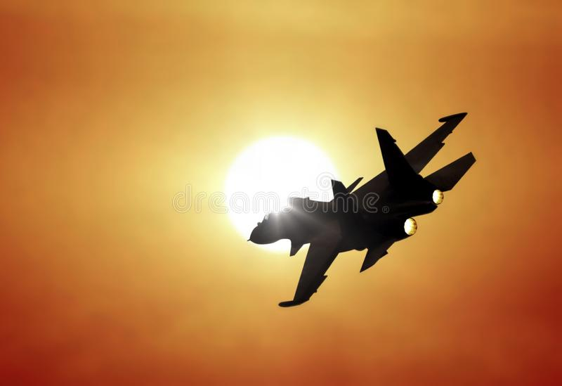 在日落下的喷气式歼击机飞行 库存图片