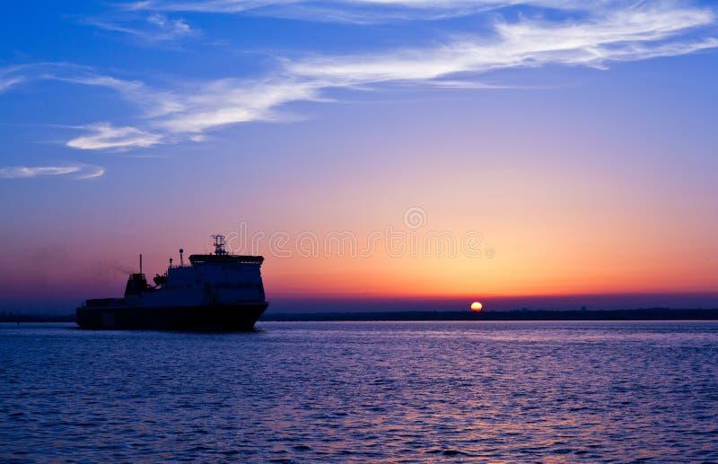 在日落下的船 免版税库存照片