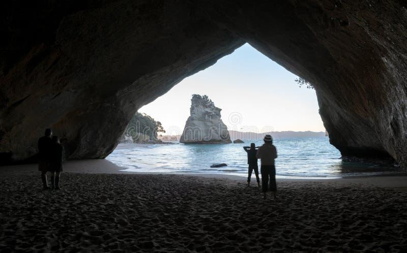 在日落与人剪影,新西兰的大教堂小海湾 库存照片