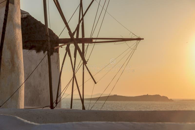 在日落与白色著名风车,米科诺斯岛基克拉泽斯,希腊的标志的海景 库存图片