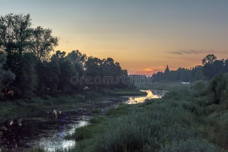 在日落以后的五颜六色的天空由河 免版税库存图片