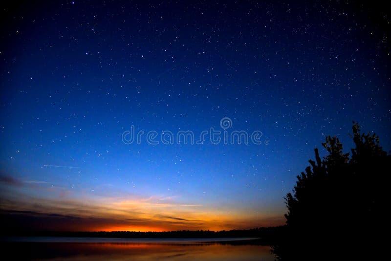 在日落以后的令人惊讶的五颜六色的天空由河 日落和夜空与很多星 库存图片