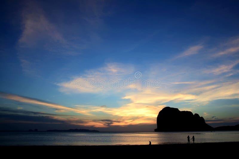 在日落以后的最后光,与山、小船在海和游人的阴影的阴影海滩神色的 库存照片