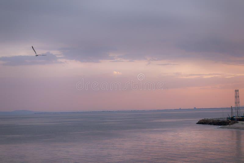 在日落以后的美好和五颜六色的海海滩微明在接近晴朗的海滩保加利亚的Nessebar 免版税库存图片