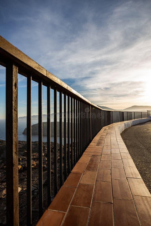 在日落光照亮的海岸峭壁的金属和木栏杆 免版税库存图片