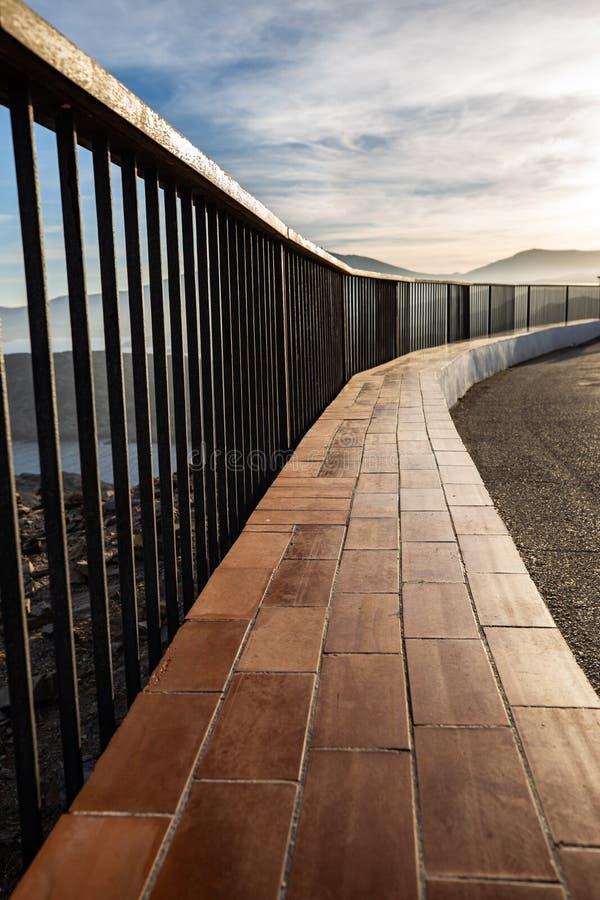 在日落光照亮的海岸峭壁的金属和木栏杆 图库摄影