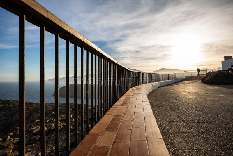 在日落光照亮的海岸峭壁的金属和木栏杆 库存图片