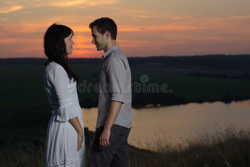 在日落和湖的夫妇 免版税库存图片