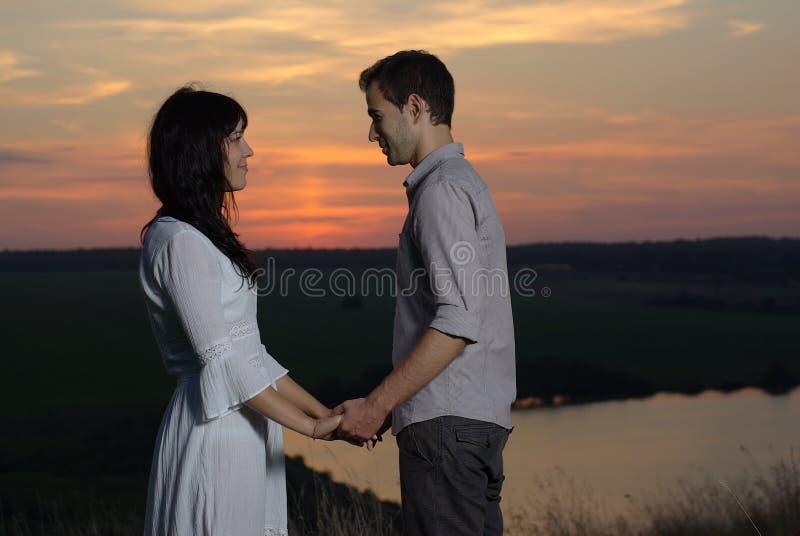 在日落和湖的夫妇 免版税库存照片