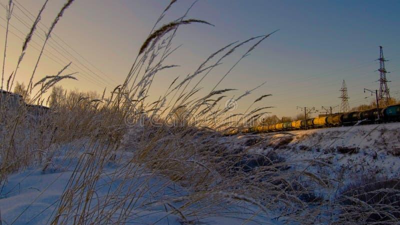 在日落在冬天、山沟和铁路 免版税库存图片