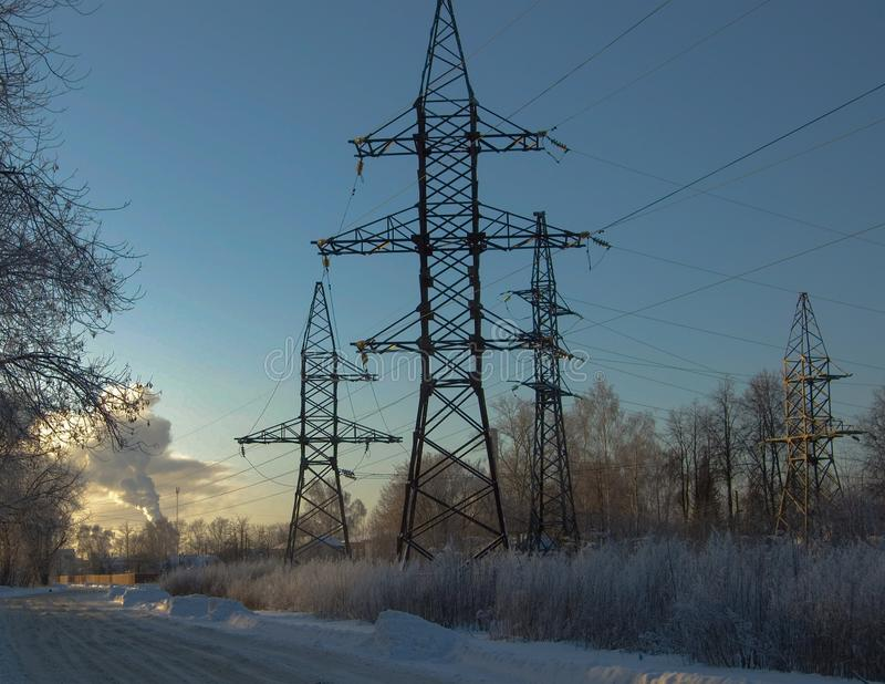 在日落在冬天,高压支持 图库摄影