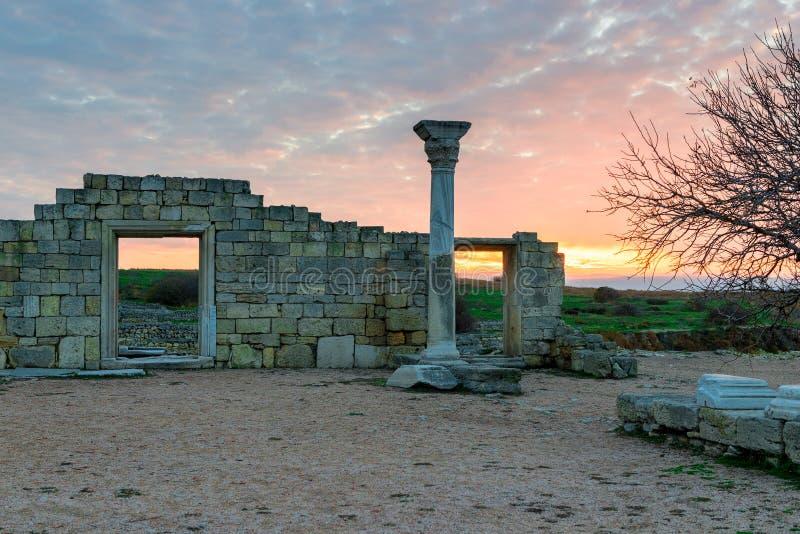 在日落在黑海附近,在背景的美丽的废墟的古老Chersonese 免版税库存照片