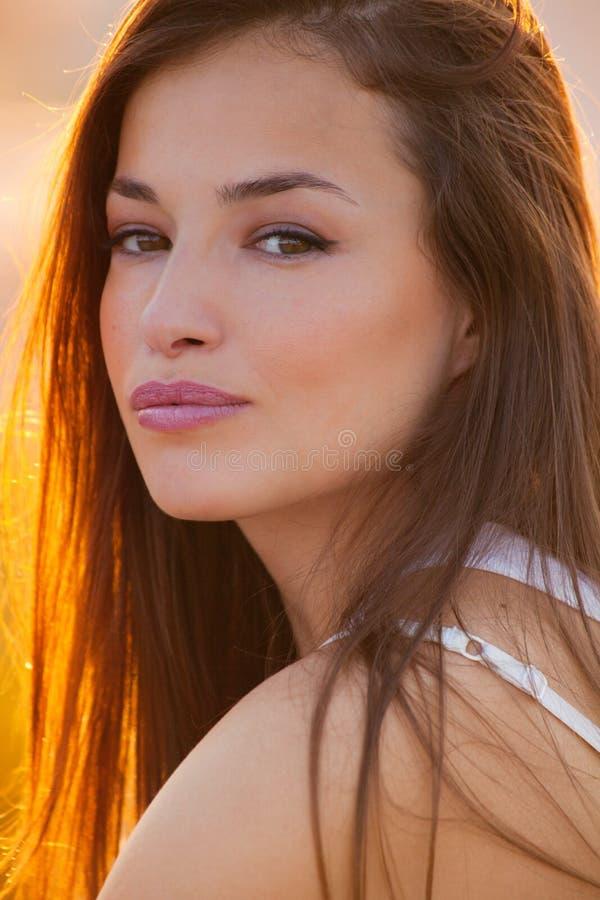 在日落夏日关闭的美丽的年轻都市女人画象 免版税库存图片