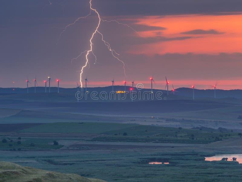 在日落天空的闪电在与风轮机和湖的小山 库存图片