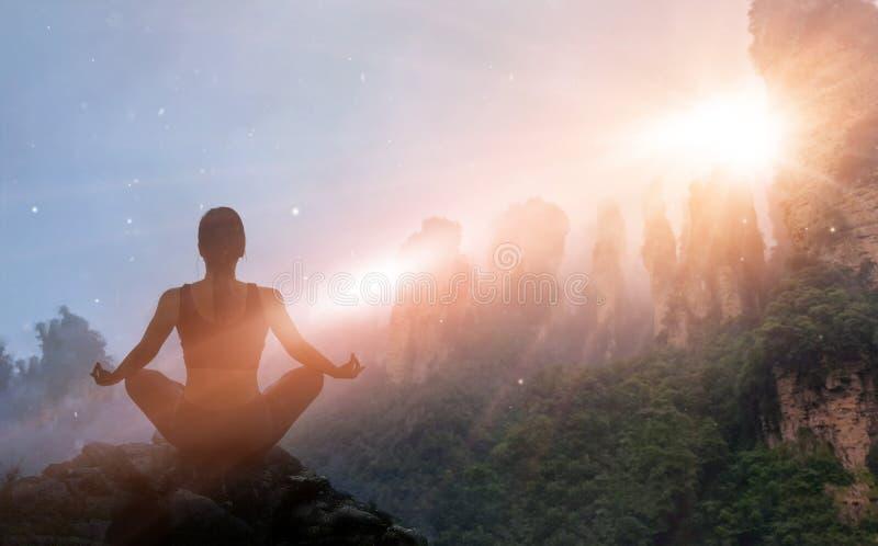 在日落山的女子思考的瑜伽与自然 室外s 免版税库存照片