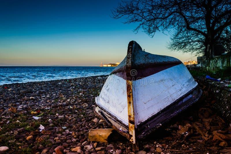 在日落岸的被扭转的渔夫划艇 免版税库存图片