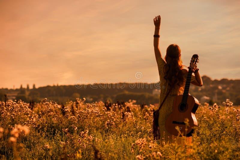 在日落时分,身穿波希米亚风格的女子在田野里拿着吉他 免版税库存照片