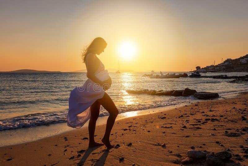 在日落时间,孕妇在海滩站立并且握她的腹部 免版税库存照片