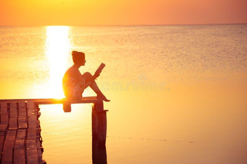 在日落时间的女孩读书 免版税库存图片