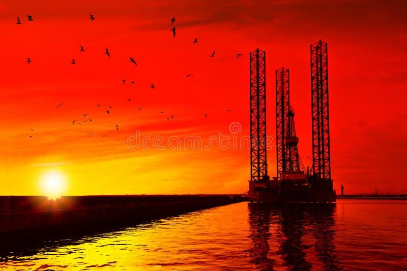 在日落的抽油装置 图库摄影