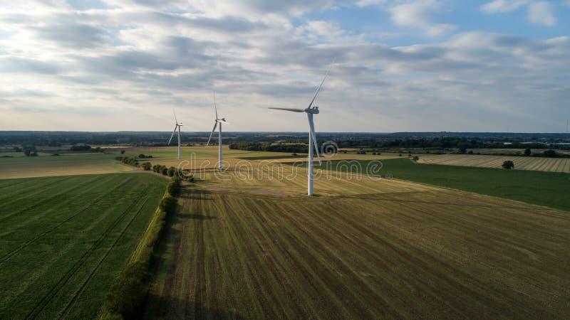 在日落期间的向着海岸的Windfarm 免版税库存照片
