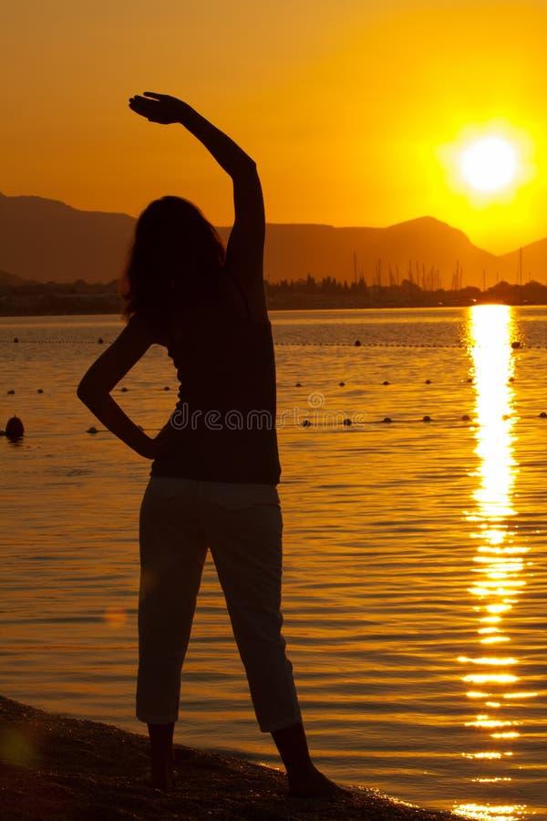 在日落期间的女子excercising的瑜伽 库存照片