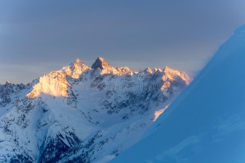 在日落期间的斯诺伊山与吹在边缘的雪 库存图片