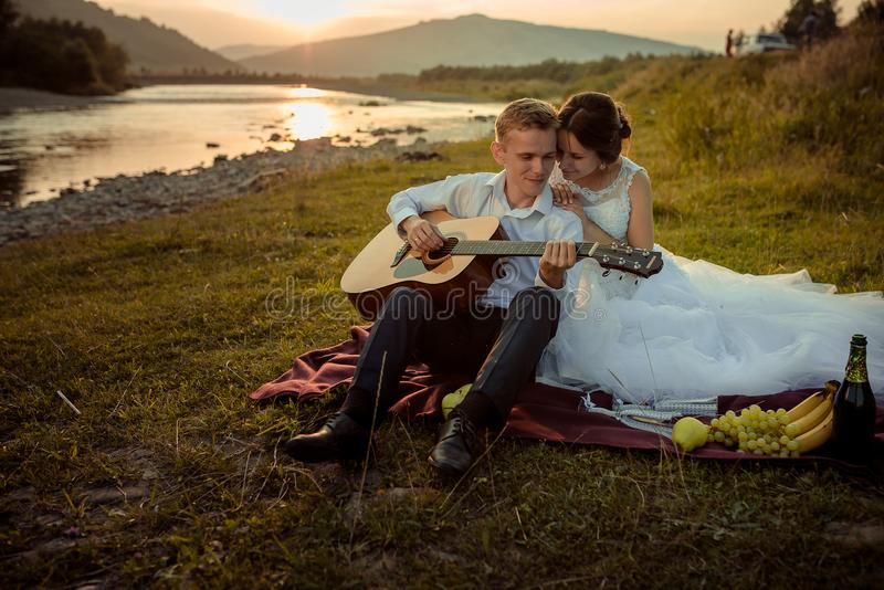 在日落期间的浪漫结婚照 英俊的新郎播放拥抱他的吉他和华美的新娘 库存图片