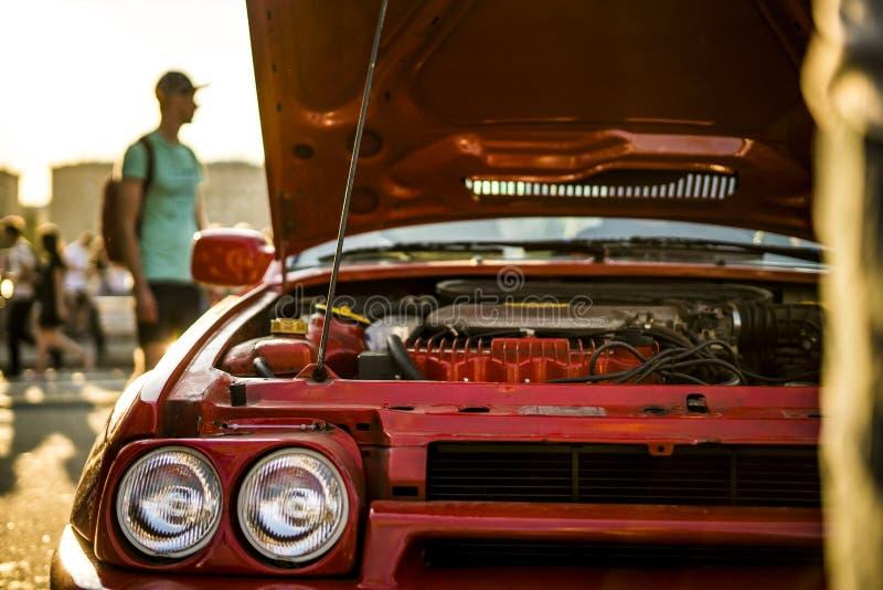 在日落期间的被打开的快速的种族肌肉汽车bonet 库存图片