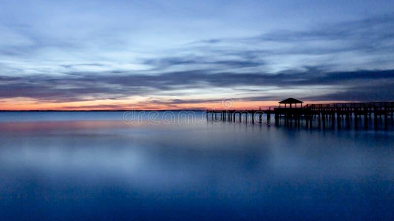在日落期间的长的曝光码头 库存图片